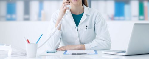 Smiling female doctor working at office desk and answering phone calls, healthcare and consulting concept